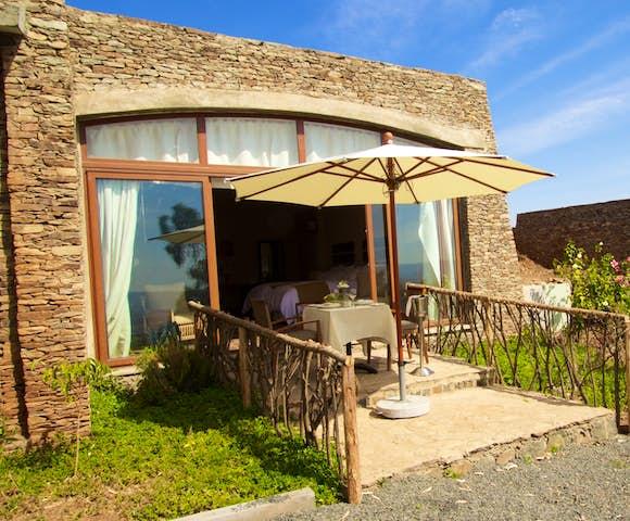 Bedroom and dining table on veranda at Gondar Hills Resort