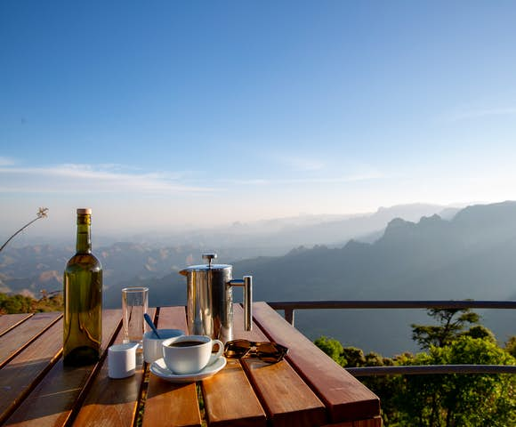 Wine and coffee on table with Simien Mountains landscape in background