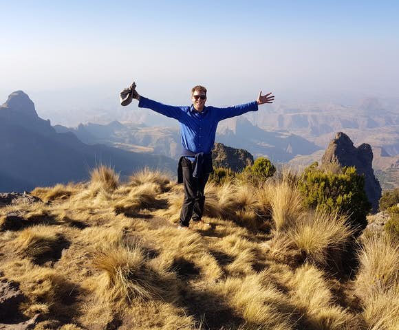 Man spreading arms in front of landscape view in the Simien Mountains