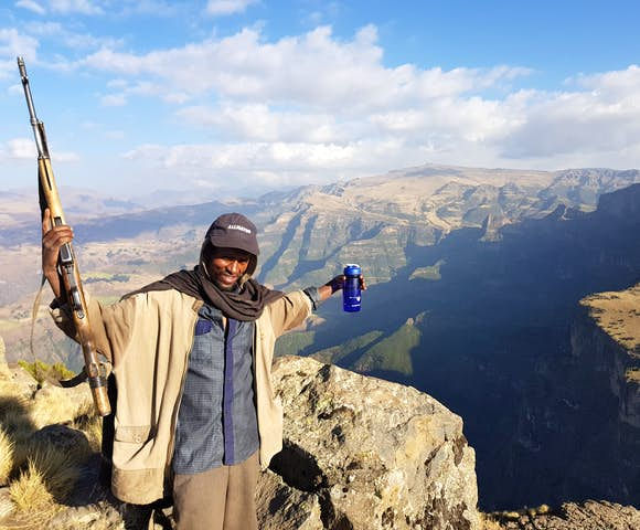 Scout with rifle spreading arms in front of landscape in the Simien Mountains