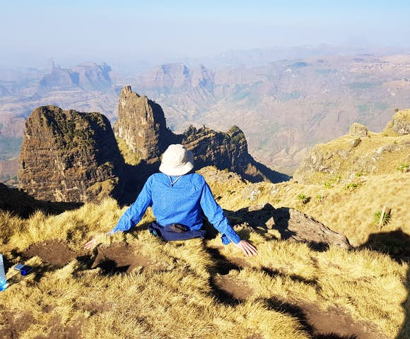 Man sitting on ledge looking at landscape in the Simien Mountains