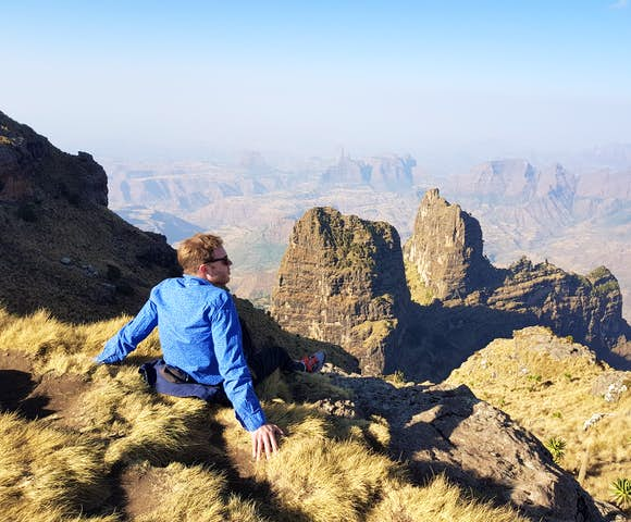 Man sitting on ledge admiring the landscape in the Simien Mountains