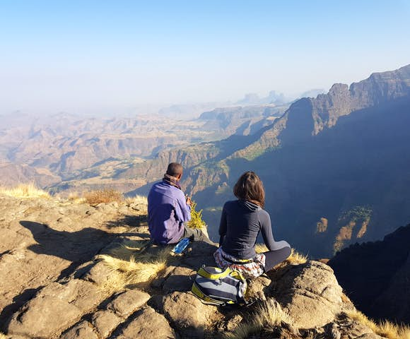 Two people sitting on cliff edge looking at the view in the Simien Mountains